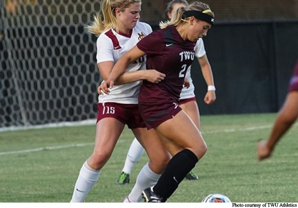 Midfielder Chelsea Martin blocks a player while straddling the ball in a game against Angelo State.