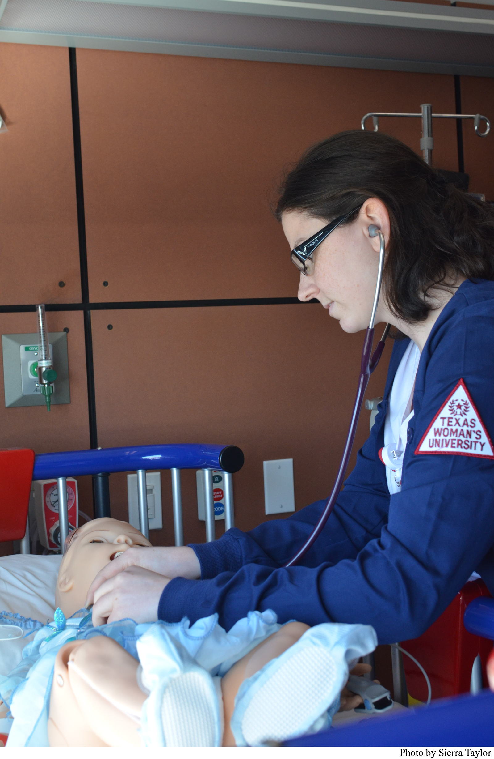 TWU Nursing student Moriah Grossmann assesses a simulation mannequin in the pediatric unit of the high fidelity lab.
