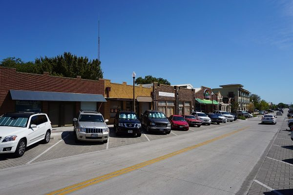 Cars parked street-side on a two-lane downtown street.